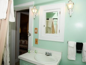 Bathroom sink under wall cabinet mirror and light sconces
