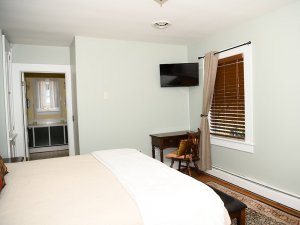 Wall-mounted television, desk, chair, and window across from footer of bed