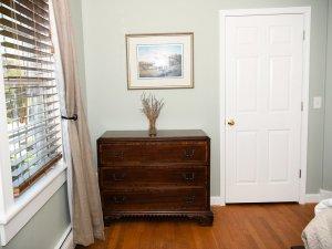 Dresser next to open curtained window in bedroom