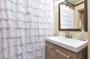 Tile shower with wood gated cabinet