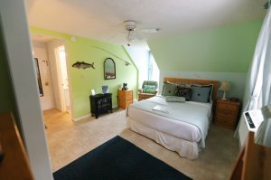 Queen-sized bed next to endtable under vaulted ceiling