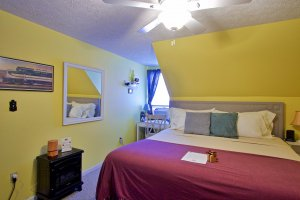 King-sized bed next to lamp in bedroom