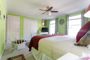 King-sized bed below ceiling fan and next to window