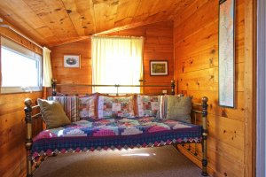 Decorative pillows against headboard with old snowshoes above