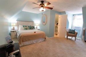 Bed next to open doorway of bedroom