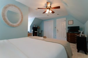 Door in bedroom between bed and window