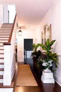 Staircase near rug, sideboard, and planter