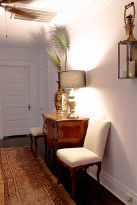 two chairs near a small antique table with a lamp