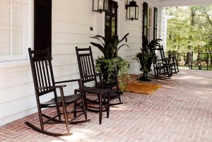 Rocking chairs and small tables on front porch