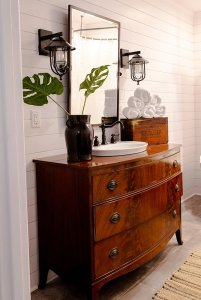 Wood countertop with sink, mirror, and towels in bathroom