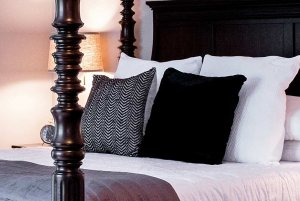 Pillows on four-post bed with tall headboard