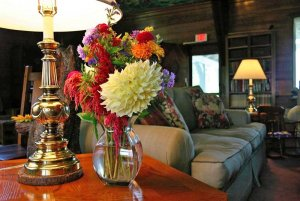 Glass vase with flowers near couch
