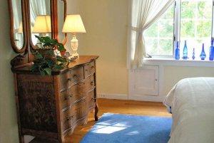 Mirrored dresser near bed