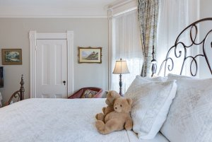 Teddy bears and pillows on bed next to window