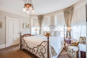 Bed infront of windows and under chandelier
