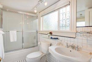 Glass door shower next to toilet and sink in bathroom