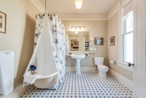 Bathtub and shower with wrap-around shower curtain in bathroom