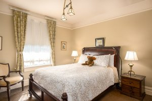 Queen bed next to window and chair in bedroom