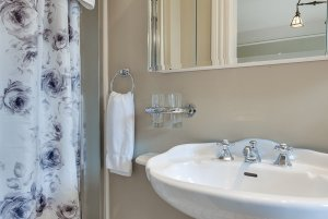 Sink next to shower curtains and hand towel
