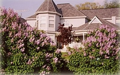 White house with trees and pink flowers