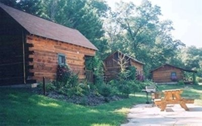 three cabins with a picnic table