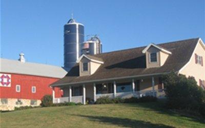 Farmhouse next to barn and silos