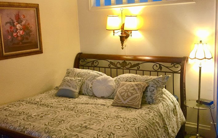 A bed with white and tan covers