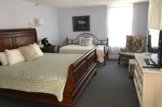 A room with a king bed and a day bed