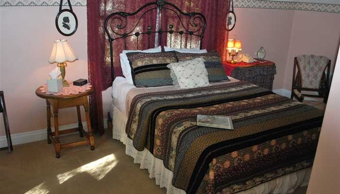bed with iron headboard at seven wives inn