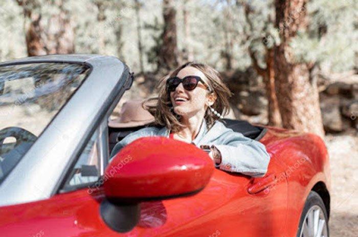 A woman driving a convertible