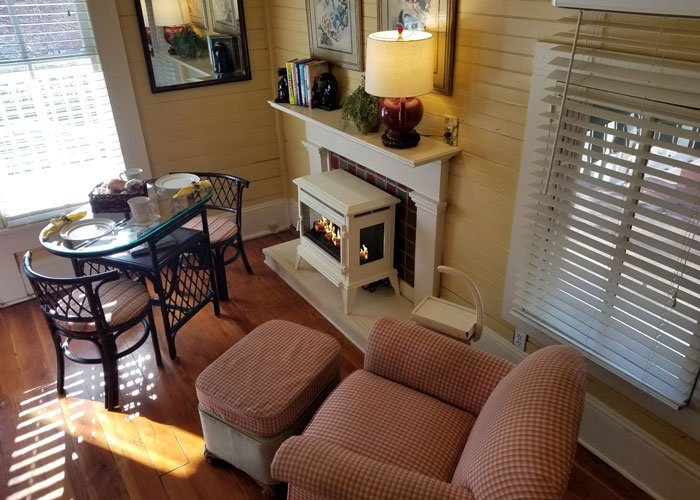 A fireplace with chairs and a table