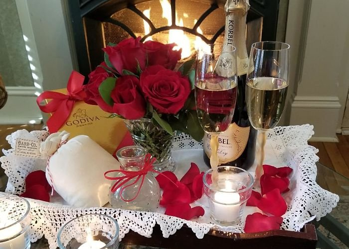 A wine bottle and glasses with flowers