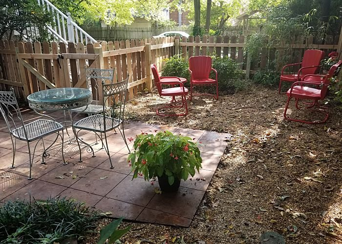 Fenced in patio with chairs and table