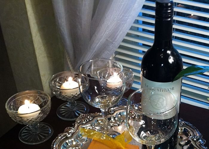 Bottle of wine with chocolates and candles
