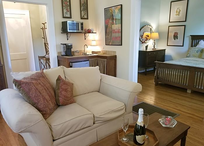 Sitting room couch with table and chairs with kitchenette