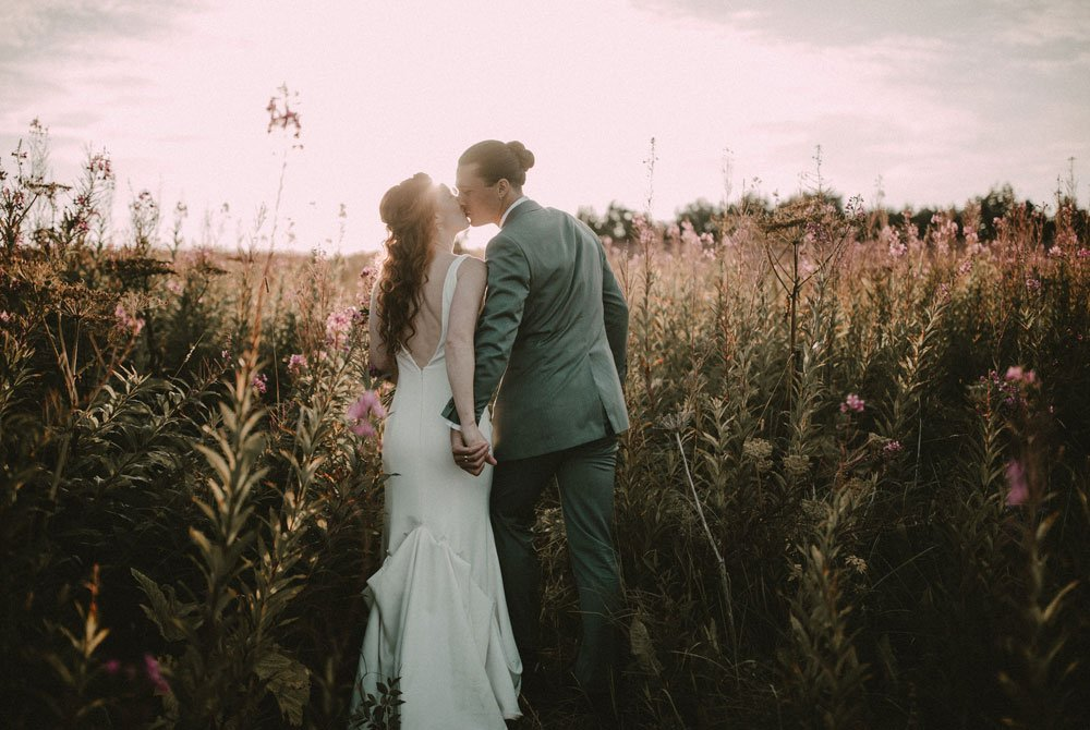 Newlywed couple kissing in the sunset
