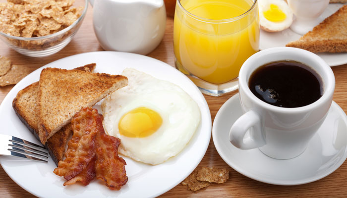Breakfast featuring toast, bacon, and an egg