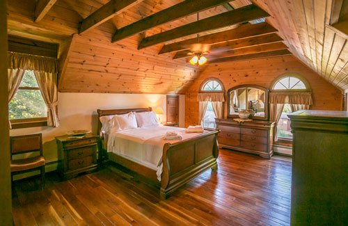 Bedroom with wood floors and overhead beams