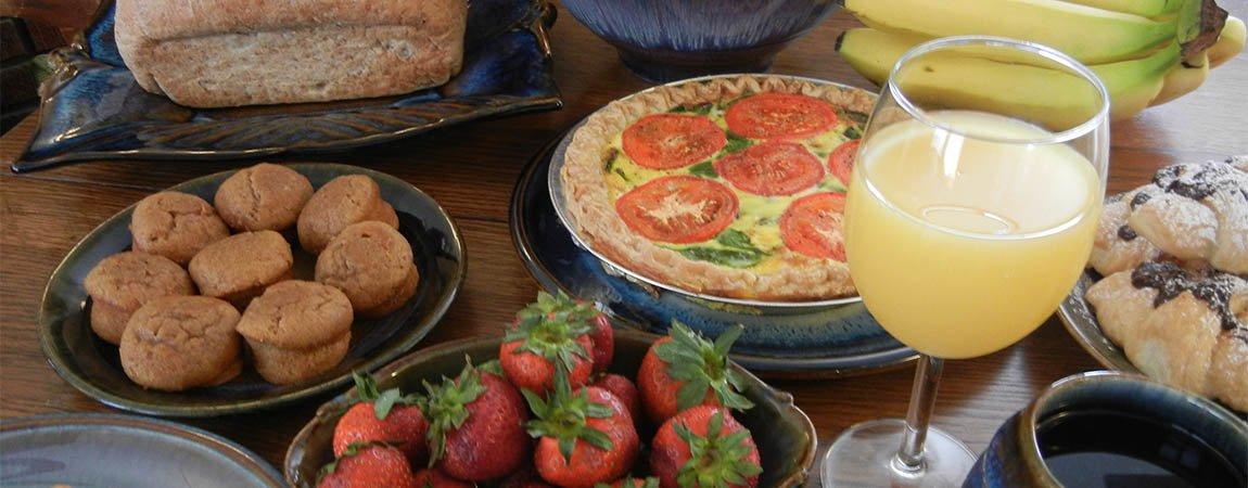 Breakfast spread with muffins, strawberries, quiche, and orange juice