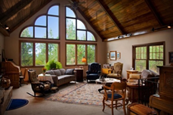 Large living room with vaulted ceiling and tall windows