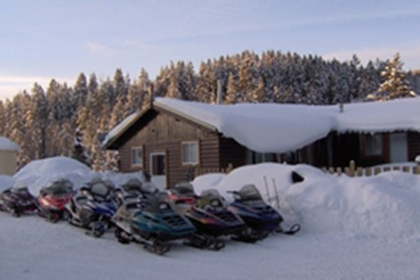 Snow-covered ski mobiles and cabin with forest in background