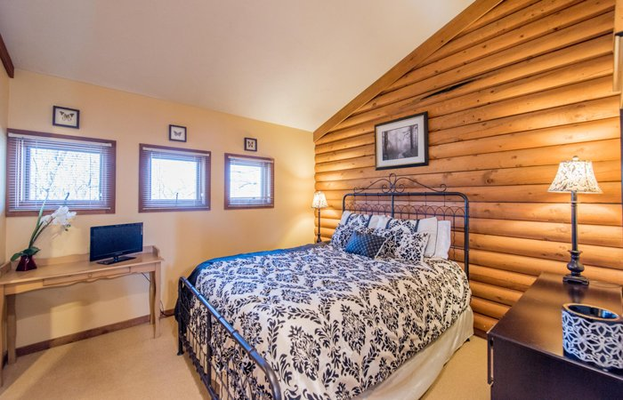 Bedroom with a log wall