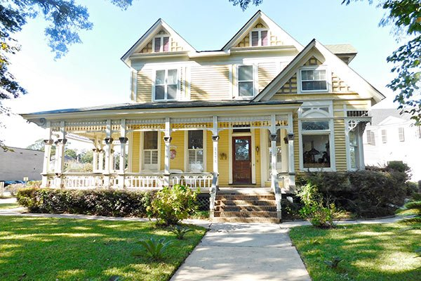 A large yellow house with wraparound porch