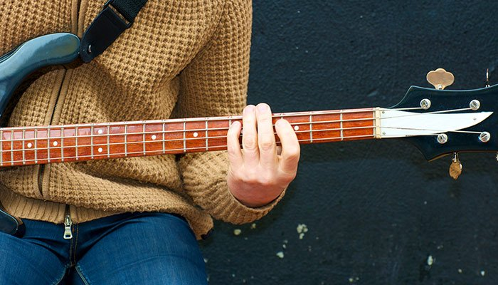 Person playing a bass guitar
