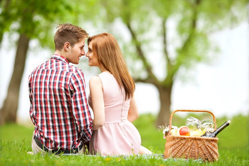 A couple holding hands while picnicking
