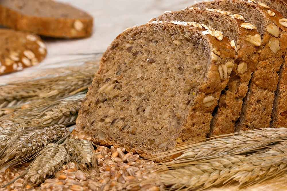 Grain bread surrounded by heads of wheat