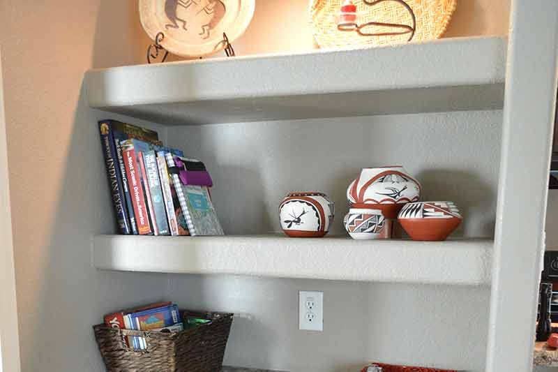 A bookshelf with books and pottery