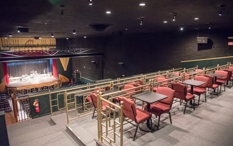 A theatre room with couples tables at the back and standard theatre seating at the front