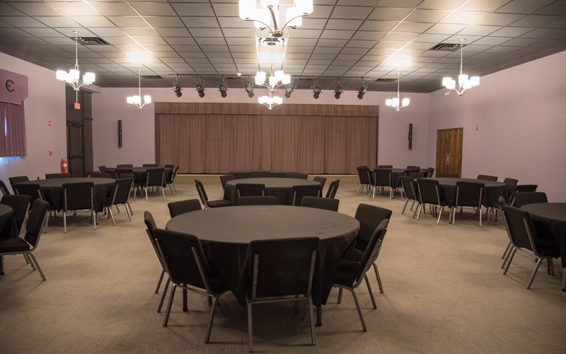 A large room set with round tables and chairs