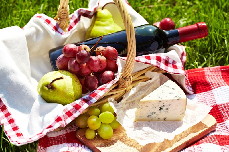 A picnic basket with wine, grapes, and cheese